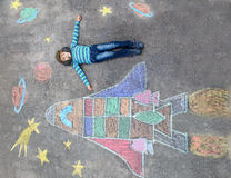 Little kid boy flying by a space shuttle chalks picture. Funny little kid boy flying in universe by a space shuttle picture painting with colorful chalks Royalty Free Stock Photography