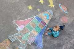 Little kid boy flying by a space shuttle chalks picture. Funny little kid boy flying in universe by a space shuttle picture painting with colorful chalks royalty free illustration