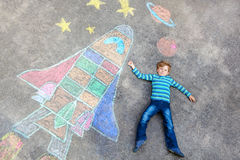 Little kid boy flying by a space shuttle chalks picture Royalty Free Stock Photography