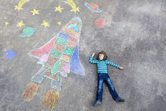 Little kid boy flying by a space shuttle chalks picture Stock Photography