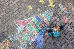 Little kid boy flying by a space shuttle chalks picture Royalty Free Stock Photos