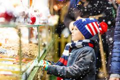 Little kid boy with gingerbread and sweets stand on Christmas market Royalty Free Stock Photo