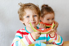 Little kid boy and girl eating healthy food watermelon Stock Images