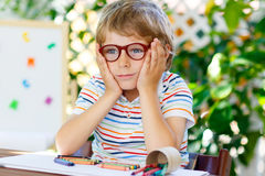 Little kid boy with glasses holding school equipment royalty free stock images