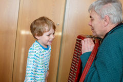 Little kid boy and grandfather playing music instrument Stock Photo