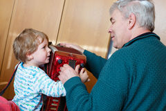 Little kid boy and grandfather playing music instrument Stock Photography