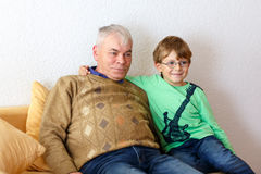Little kid boy and grandfather watching tv at home. Stock Photo