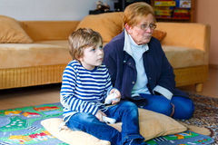 Little kid boy and grandmother playing video game console Royalty Free Stock Photos