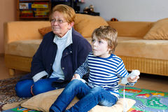 Little kid boy and grandmother playing video game console Royalty Free Stock Image