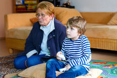 Little kid boy and grandmother playing video game Stock Photos