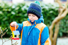 Little kid boy hanging bird house on tree for feeding in winter Royalty Free Stock Image