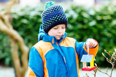 Little kid boy hanging bird house on tree for feeding in winter Stock Photos