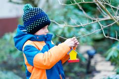 Little kid boy hanging bird house on tree for feeding in winter Royalty Free Stock Photos
