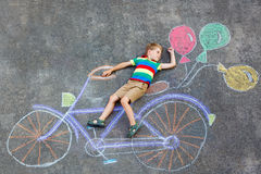 Little kid boy having fun with bicycle chalks picture on ground Stock Photography