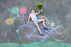 Little kid boy having fun with bicycle chalks picture on ground. Happy little kid boy having fun with bicycle and air balloons picture drawing with colorful Royalty Free Stock Photos