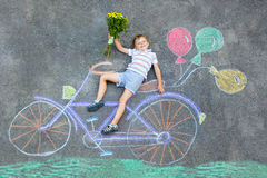 Little kid boy having fun with bike chalks picture Royalty Free Stock Images
