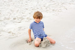 Little kid boy having fun with building sand castles Stock Photo