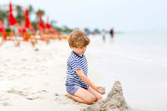 Little kid boy having fun with building sand castles Royalty Free Stock Image