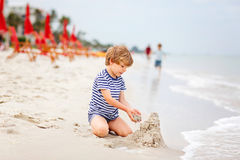 Little kid boy having fun with building sand castles Stock Image