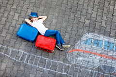 Little kid boy having fun with fast train picture drawing with colorful chalks on asphalt. Child painting with chalk and crayon and going on vacations Stock Photos