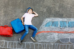 Little kid boy having fun with fast train picture drawing with colorful chalks on asphalt. Child painting with chalk and crayon and going on vacations Stock Image