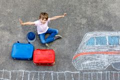 Little kid boy having fun with fast train picture drawing with colorful chalks on asphalt. Child painting with chalk and crayon and going on vacations Stock Photo