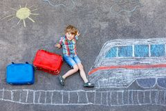 Little kid boy having fun with fast train picture drawing with colorful chalks on asphalt. Child painting with chalk and crayon and going on vacations Royalty Free Stock Image