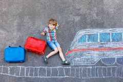 Little kid boy having fun with fast train picture drawing with colorful chalks on asphalt. Child painting with chalk and crayon and going on vacations Stock Images
