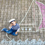 Little kid boy having fun with ship picture drawing with chalk. Adorable little kid boy playing with colorful chalks and painting ship or boat picture. Creative stock images