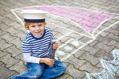 Little kid boy having fun with ship picture drawing with chalk. Funny little kid boy of four years having fun with ship or boat picture drawing with chalk stock photos