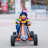 Little kid boy having fun on toy race car outdoors Royalty Free Stock Photo