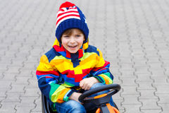Little kid boy having fun on toy race car outdoors Royalty Free Stock Photography