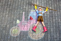 Little kid boy having fun with tractor chalks picture. Happy little kid boy in straw hat and rain boots having fun with tractor picture drawing with colorful Royalty Free Stock Photo