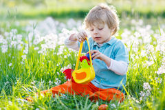 Little kid boy having fun with traditional Easter egg hunt Stock Photos