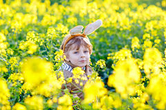 Little kid boy having fun with traditional Easter egg hunt Stock Photography