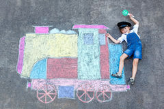 Little kid boy having fun with train chalks picture Stock Photos