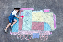 Little kid boy having fun with train chalks picture Stock Photography