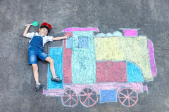 Little kid boy having fun with train chalks picture Stock Image