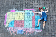 Little kid boy having fun with train chalks picture Stock Photo