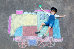 Little kid boy having fun with train chalks picture. Happy little kid boy having fun with train or steam locomotive picture drawing with colorful chalks on Royalty Free Stock Photos