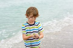 Little kid boy having fun on tropical beach Stock Photo
