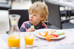 Little kid boy having healthy breakfast in hotel restaurant or c Royalty Free Stock Photos