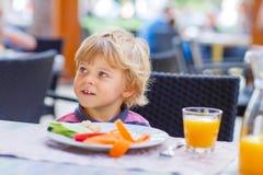 Little kid boy having healthy breakfast in restaurant Stock Photo
