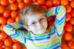 Little kid boy with healthy mandarin oranges fruits Royalty Free Stock Images