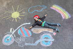 Little kid boy in helmet with motorcycle chalk Royalty Free Stock Photography