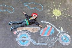 Little kid boy in helmet with motorcycle chalk picture. Happy kid boy in race helmet having fun with motorcycle picture drawing with colorful chalks. Children Stock Image