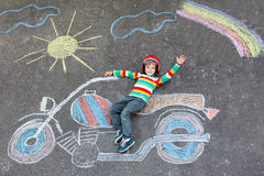 Little kid boy in helmet with motorcycle chalks Stock Photos