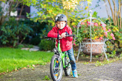 Little kid boy in helmet riding with his bicycle in the city Stock Photos