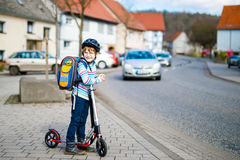Little kid boy in helmet riding with his scooter in the city Stock Images