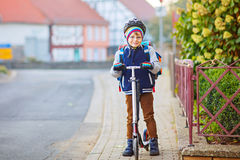 Little kid boy in helmet riding with his scooter in the city Stock Photos